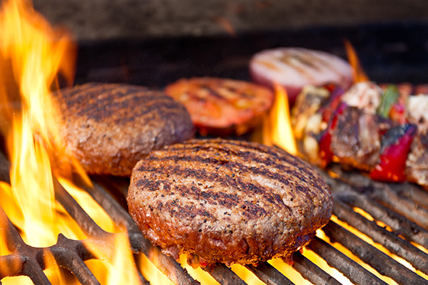 Closeup of burger, other foods on a charcoal grill